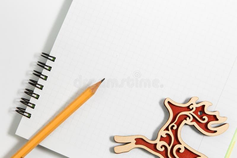 Anteckningsboken och guling ritar med röda trähjortar på en vit backg arkivfoton
