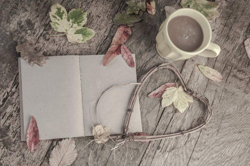 Anteckningsboken och kaffe på trätabellen dekorerade med torkade sidor royaltyfria foton