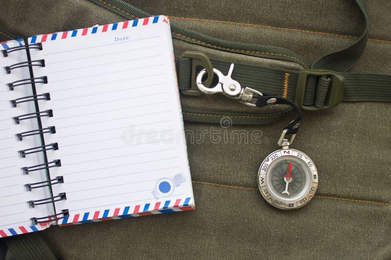 Anteckningsboken och kompasset med säkerhet hakar på rem av en ryggsäck royaltyfria bilder