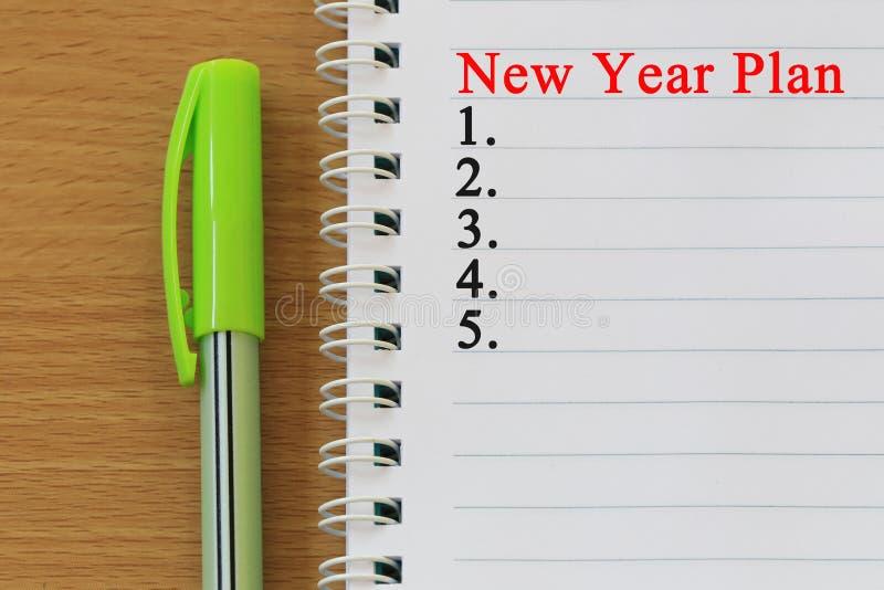 Anteckningsboken och pennan som förläggas på det wood skrivbordet och nytt år, planerar text royaltyfri foto