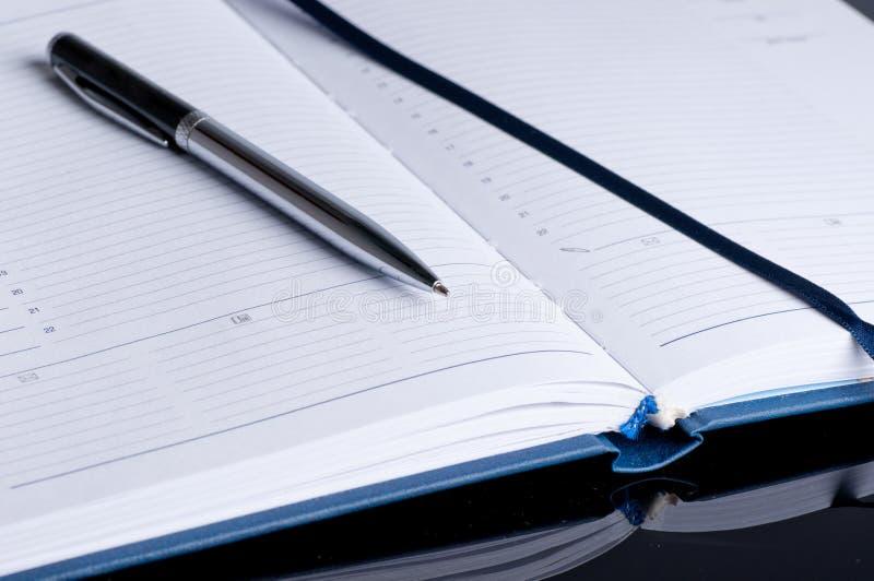 Anteckningsboken och skrivar i nära övre för sammansättning arkivbild