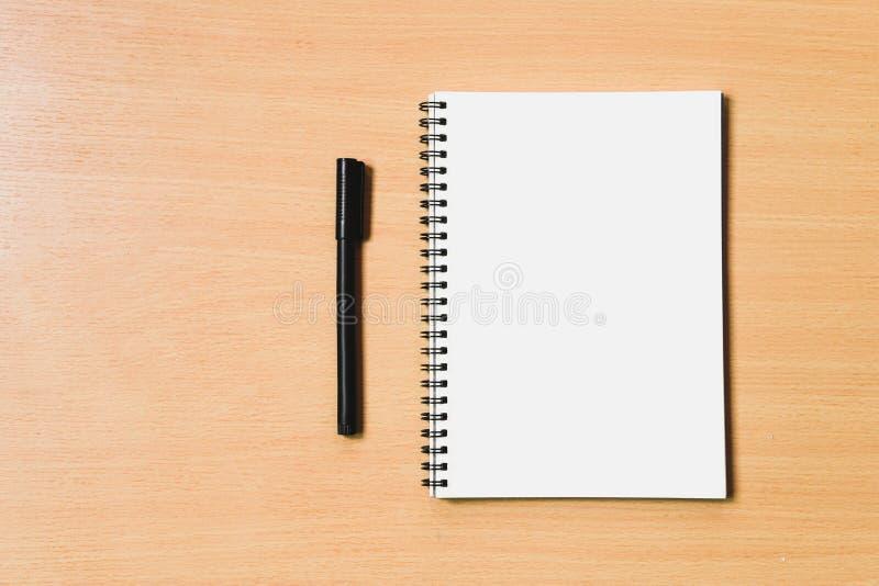 Anteckningsbokpapper med den tomma sidan för copyspace- och blakcpennan för n arkivfoton