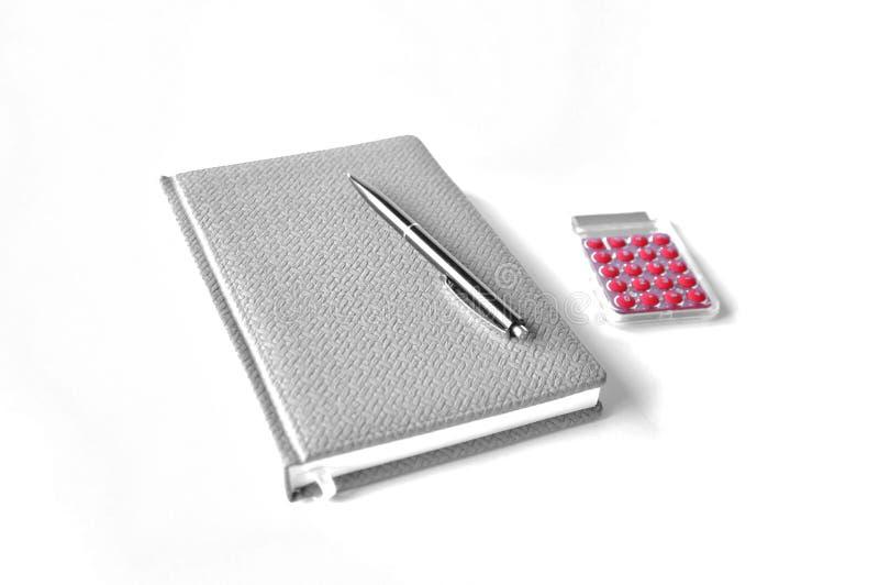 Anteckningsbokpennan och räknemaskinen är på tabellen royaltyfri foto