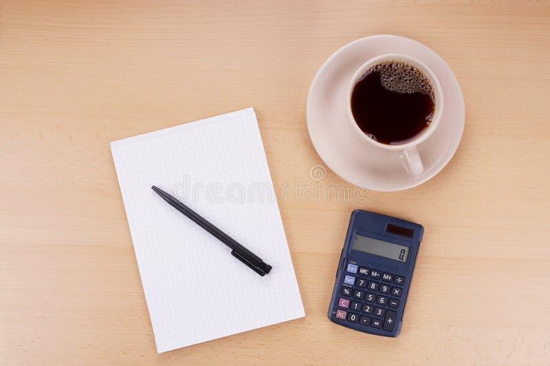 Anteckningsbokräknemaskin och kaffe arkivbild