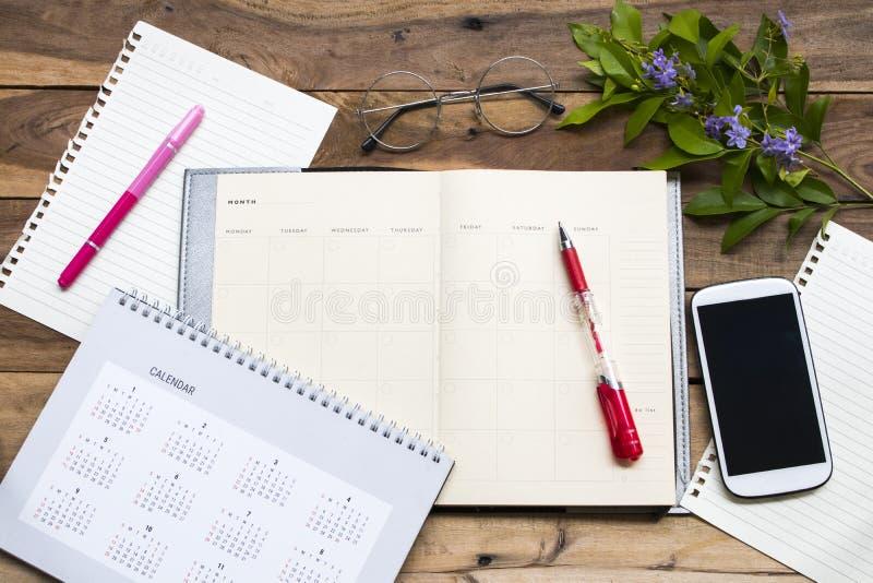 Anteckningsbokstadsplanerare, handstilpapper och mobiltelefon för affärsarbete arkivbilder