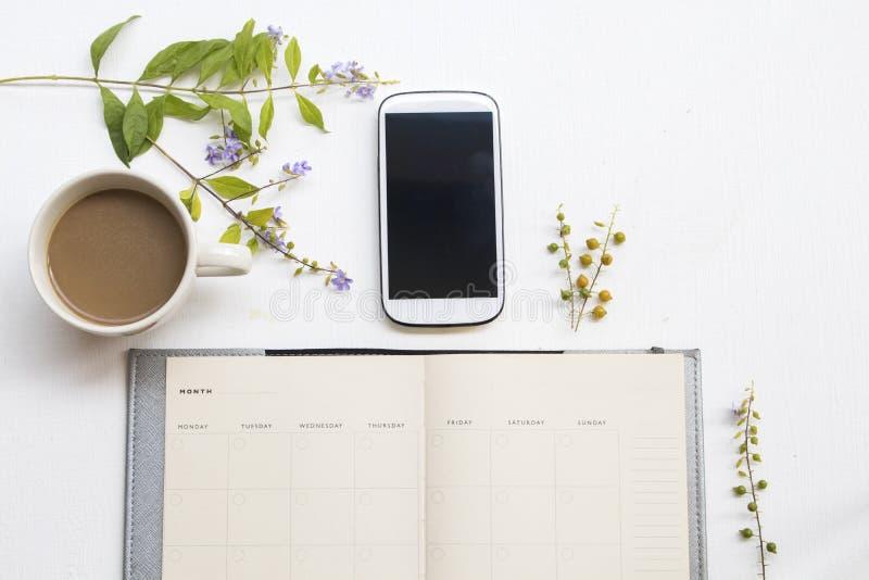 Anteckningsbokstadsplanerare med mobiltelefonen för affärsarbete och purpurfärgade blommor royaltyfri foto