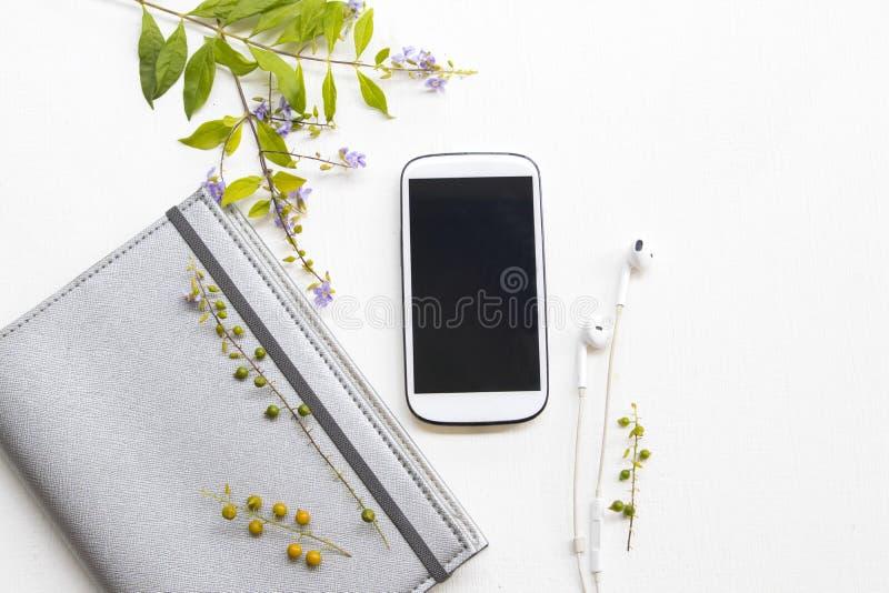 Anteckningsbokstadsplanerare med mobiltelefonen för affärsarbete och purpurfärgade blommor arkivbilder