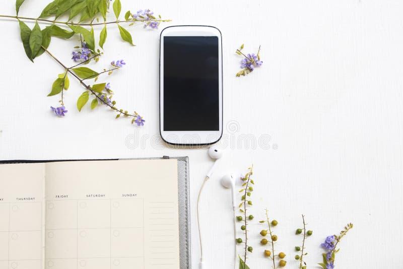 Anteckningsbokstadsplanerare med mobiltelefonen för affärsarbete och purpurfärgade blommor royaltyfri bild