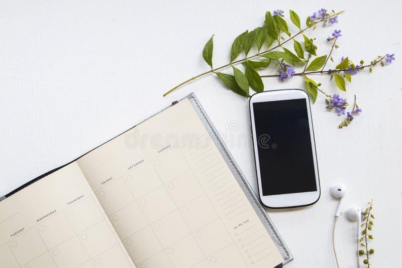 Anteckningsbokstadsplanerare med mobiltelefonen för affärsarbete och purpurfärgade blommor arkivfoto
