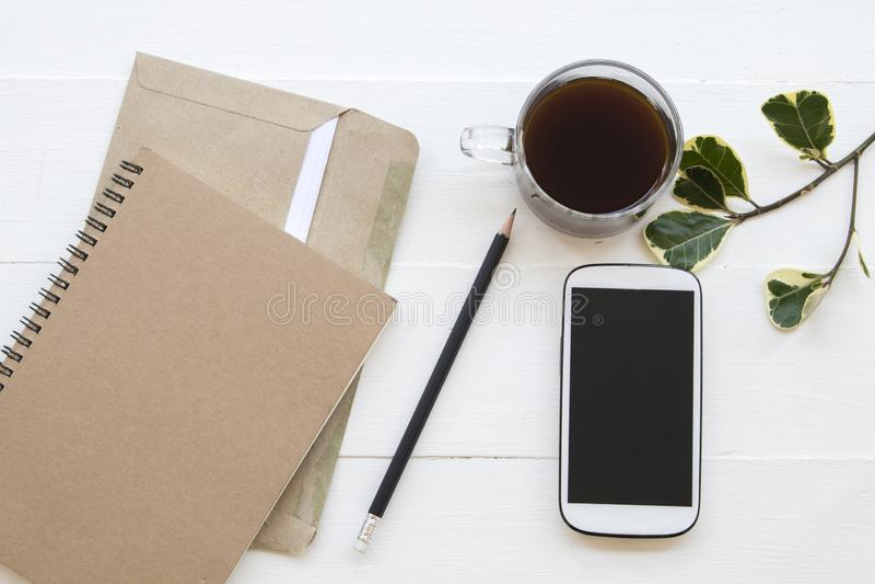 Anteckningsbokstadsplanerare, mobiltelefon, bokstav för affärsarbete på kontorsskrivbordet royaltyfri foto