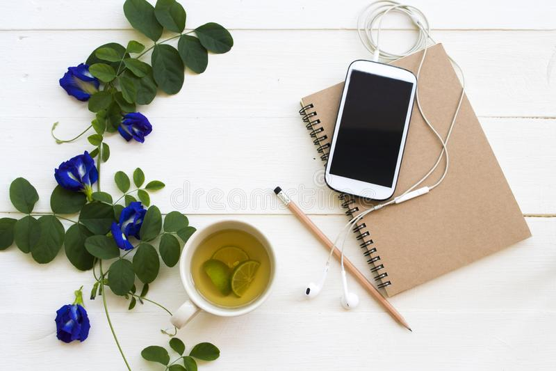 Anteckningsbokstadsplanerare, mobiltelefon för affärsarbete, växt- sund drink arkivbild