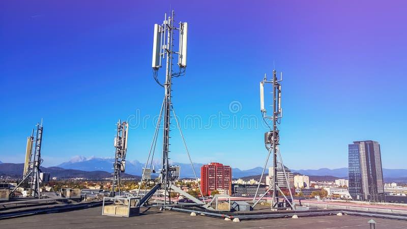 Antena celular de la red que irradia y que difunde ondas fuertes de la señal del poder sobre la ciudad fotos de archivo libres de regalías