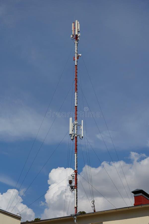 Antena da rede de rádio do celular no sinal de transmissão de construção do telhado sobre a cidade foto de stock royalty free