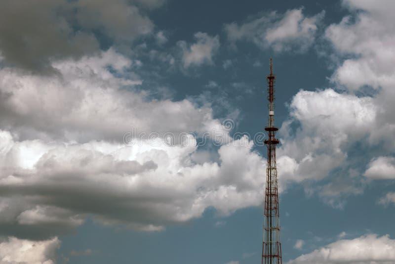 Antena da torre de rádio em um fundo do céu azul com nuvens brancas Equipamento de telefone global do transmissor da telecomunica fotografia de stock royalty free
