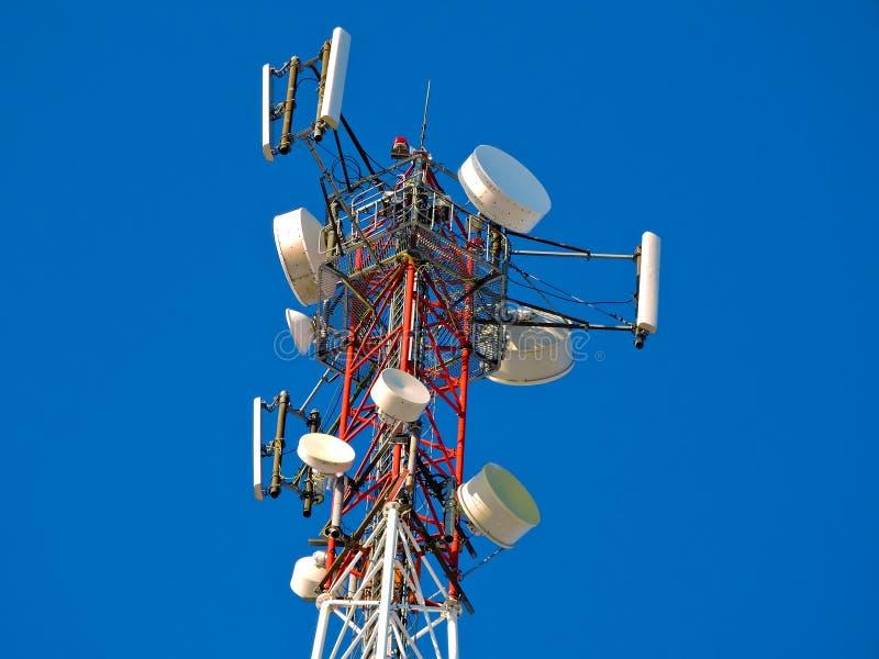 Antena de la célula, transmisor Torre móvil de radio de las telecomunicaciones TV contra el cielo azul imagen de archivo
