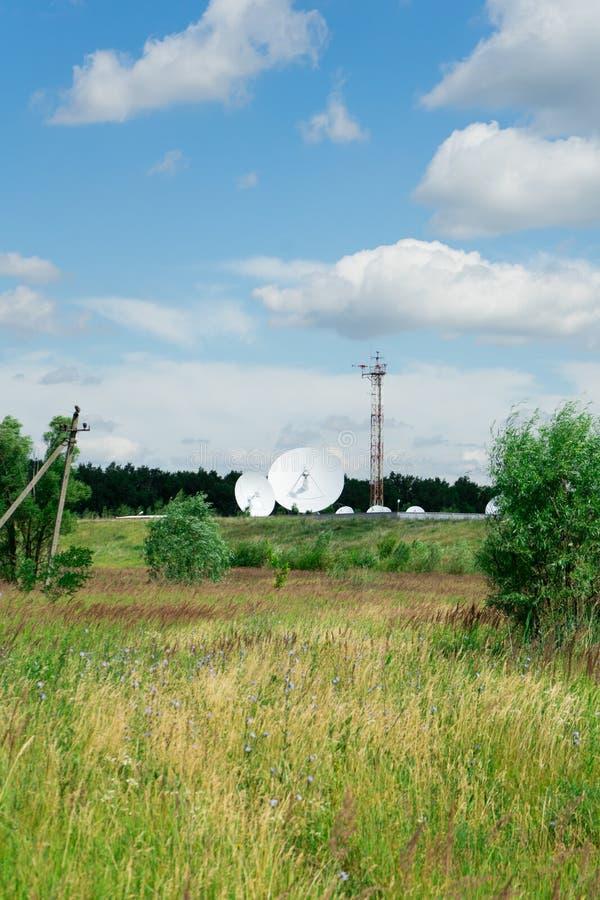 Antena de satélite en el fondo del cielo azul y del prado verde foto de archivo libre de regalías