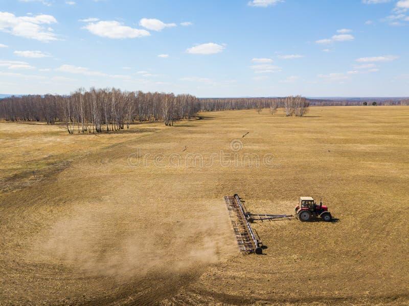 Antena do trator vermelho com um arado arrastado para segar e remover ervas daninhas de campos para a agroindústria da cor amarel fotos de stock royalty free