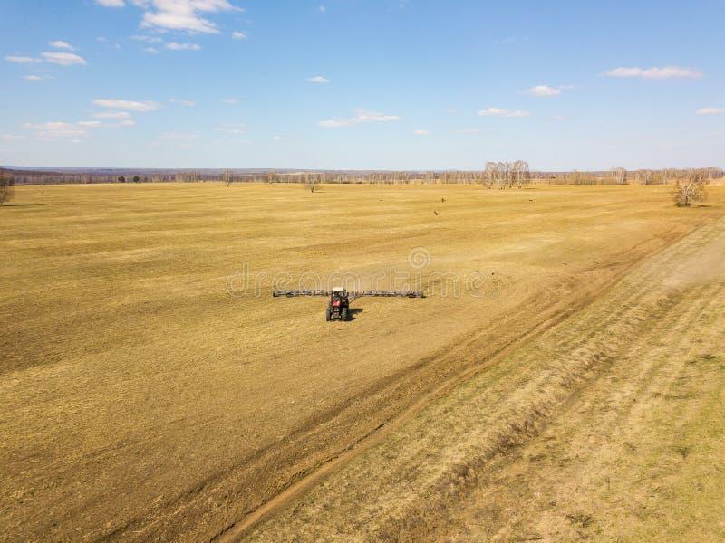 Antena do trator vermelho com um arado arrastado para segar e remover ervas daninhas de campos para a agroind?stria da cor amarel fotos de stock