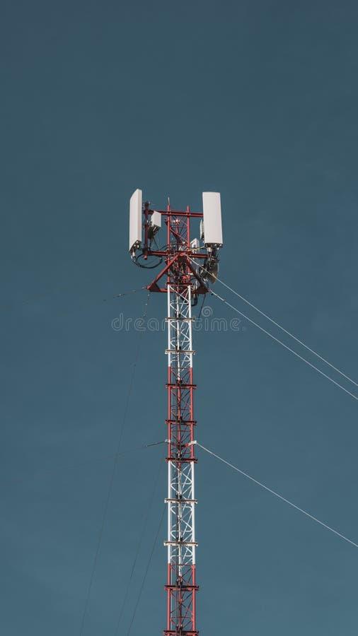 Antena móvel da torre do rádio da telecomunicação no fundo vasto do céu azul Equipamento de telefone global do Internet do transm imagens de stock