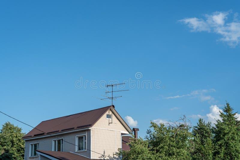 Antena no telhado de uma casa rural contra o céu azul e as nuvens brancas imagem de stock royalty free