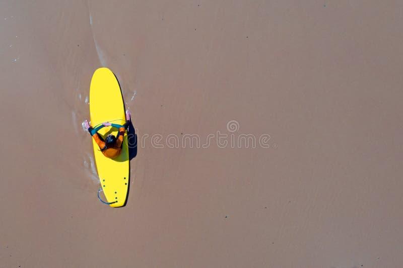 Antena od surfingowa relaksuje na jej surfboard przy atlantyckim oceanem fotografia stock