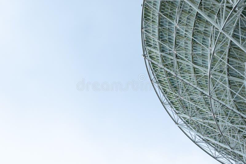 Antena parabólica de radio blanca enorme aislada contra un cielo azul brillante imágenes de archivo libres de regalías