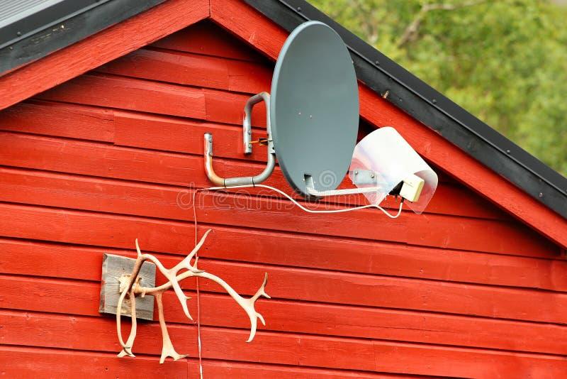 Antena parabólica e chifres decorativos na parede de madeira imagens de stock royalty free