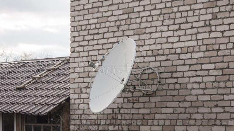 A antena parabólica montou em uma parede de tijolo imagens de stock royalty free