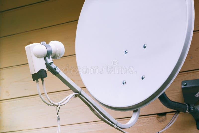Antena parabólica na parede de uma casa de campo fotografia de stock
