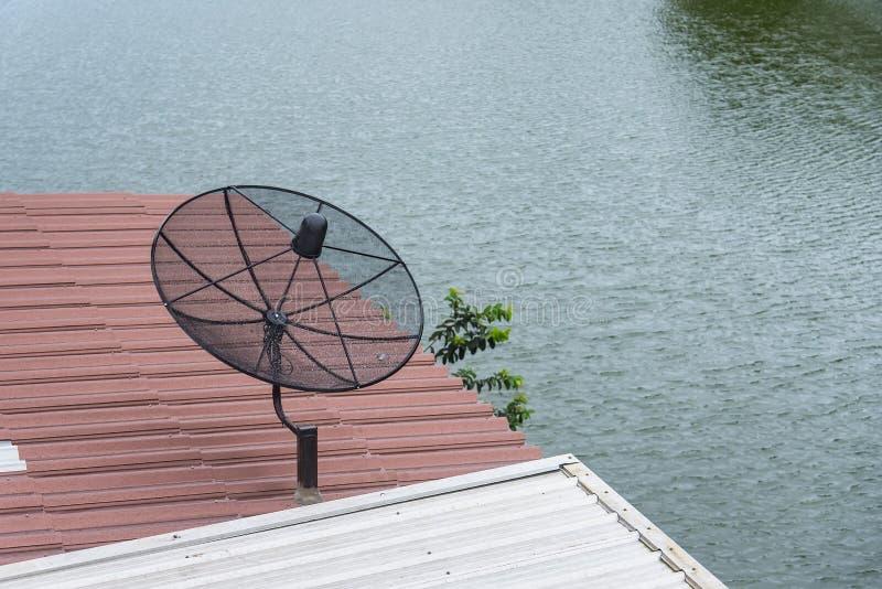 Antena parabólica no telhado de uma casa de madeira A antena parabólica é um dispositivo para receber sinais da tevê foto de stock