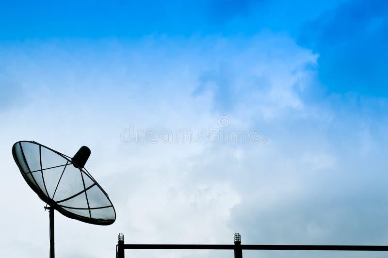 Antena parabólica preta ou antenas da tevê na construção com o céu azul nebuloso imagens de stock