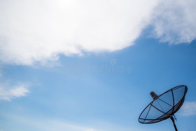 Antena parabólica, receptor do sinal da tevê em um fundo claro do céu fotografia de stock royalty free