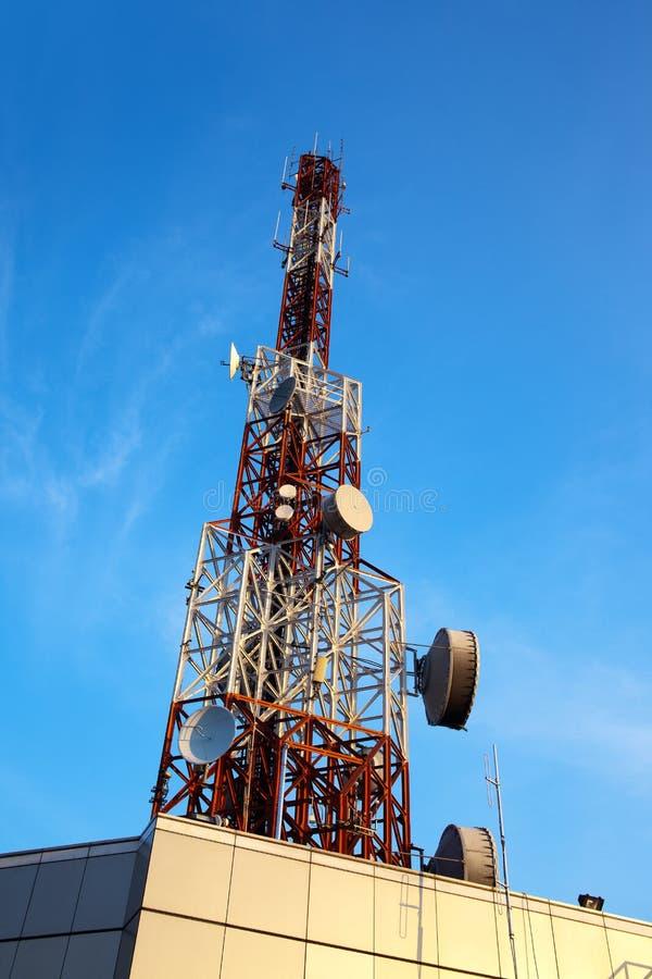 Antena roja y blanca (torre celular) debajo del cielo azul. imagen de archivo