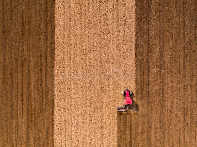 Antena strzał ciągnikowy uprawowy pole przy wiosną zdjęcie stock