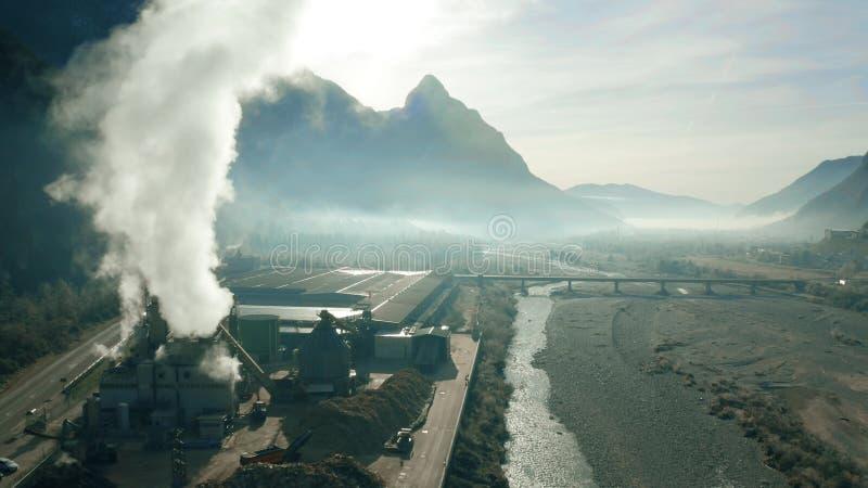 Antena strzał lotniczego zanieczyszczania drewniany zakład przeróbki w rzecznej dolinie, północny Włochy fotografia royalty free