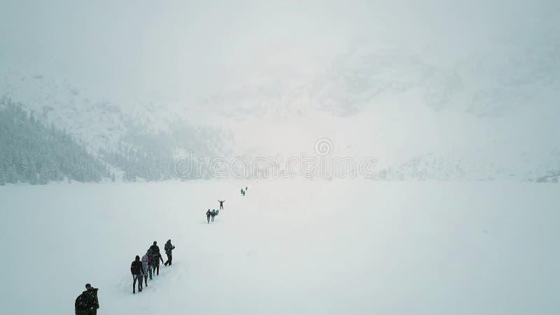 Antena strzał unrecognizable ludzie wycieczkuje na zamarzniętym halnym jeziornym Dennym oku w śniegu, Polska obraz royalty free