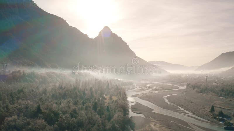 Antena strzelał piękna mglista rzeczna dolina w Alps w northeastern Włochy obrazy royalty free