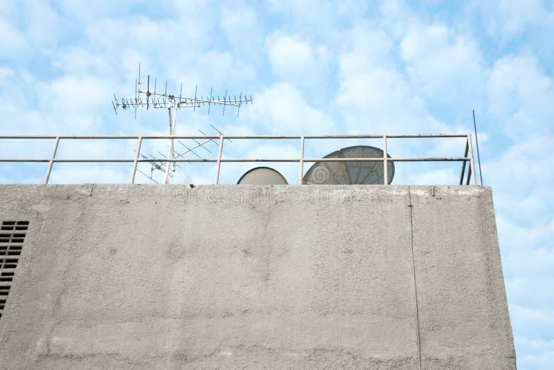 Antena y satélite en el edificio foto de archivo