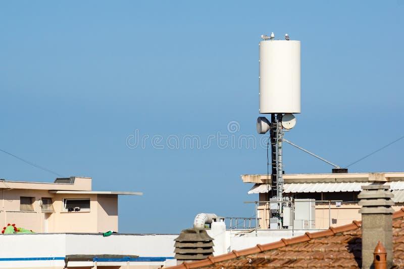 Antenas da rede de rádio do celular no sinal de transmissão de construção do telhado sobre a cidade imagem de stock royalty free