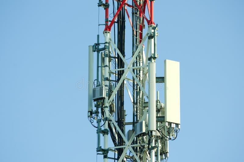 Antenas de la telecomunicación al aire libre en el cierre alto de la construcción del polo del metal rojo y blanco para arriba foto de archivo