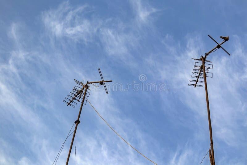 Antenas de televisión en la azotea y cielo azul fotografía de archivo