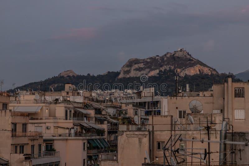 Antenas de televisión sobre edificios de Atenas con la montaña Lycabettus en segundo plano foto de archivo