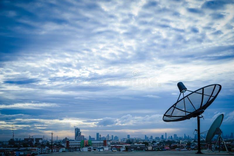 Antenn för satellit- maträtt överst av byggnaden i stadsområde arkivfoton
