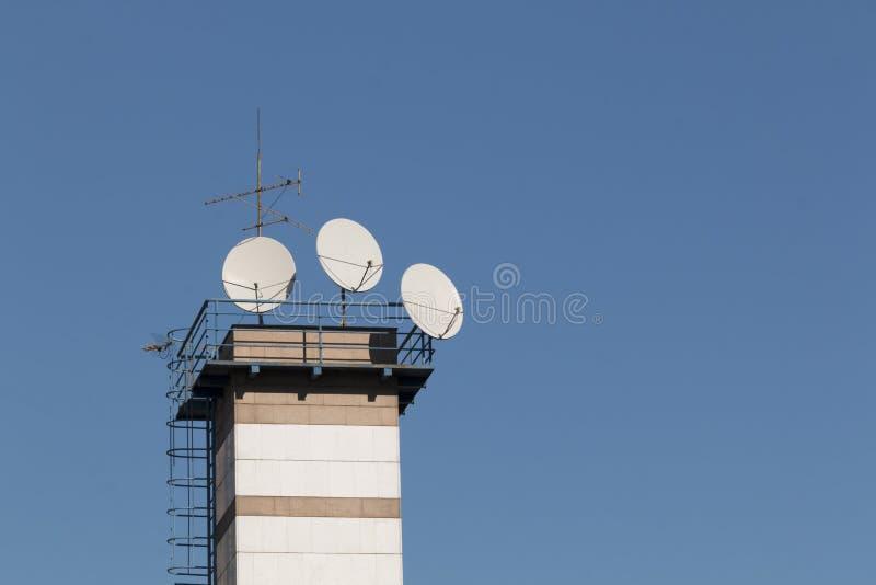 Antenn för satellit- maträtt överst av byggnaden i stadsområde på den soliga dagen royaltyfria foton