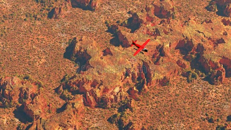 Antenna dell'aeroplano rosso che sorvola il paesaggio asciutto del deserto immagini stock