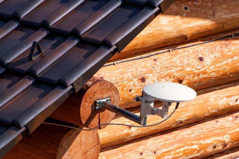 Antenna della televisione via satellite su una casa di legno Trasmissione del segnale della TV Accesso Internet La telecomunicazi immagini stock