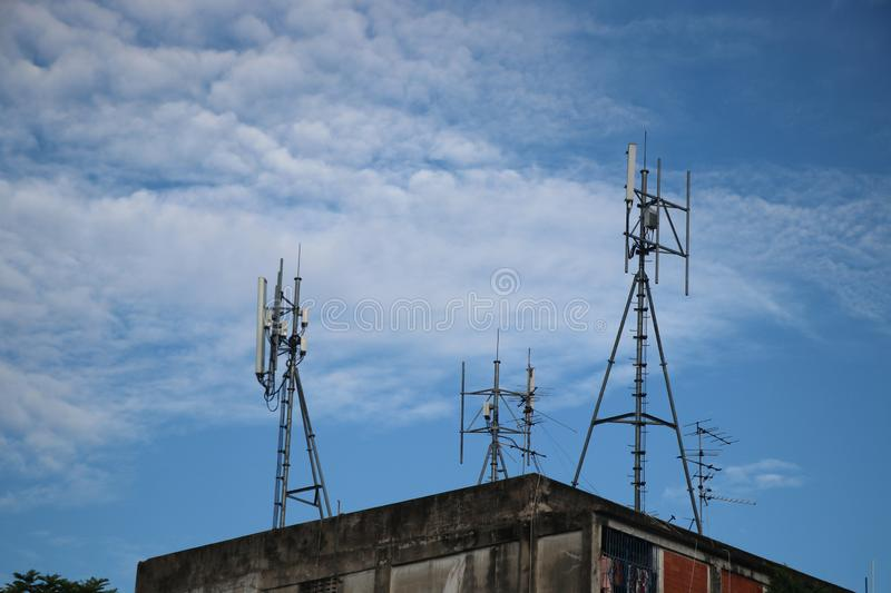 Antenna digital on building for the wireless communication with blue sky background. Antenna digital tower on building for the wireless communication with blue stock photography