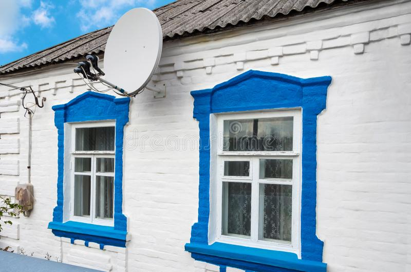 Antenna on farmhouse. A satellite dish capable of accepting three satellites on the wall of the rural house stock photography