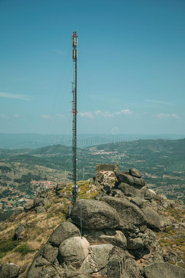 Antenna on hilltop covered by rocks and bushes in Monsanto. Antenna on hilltop covered by rocks and dry bushes, with countryside landscape and the Monsanto roofs stock images