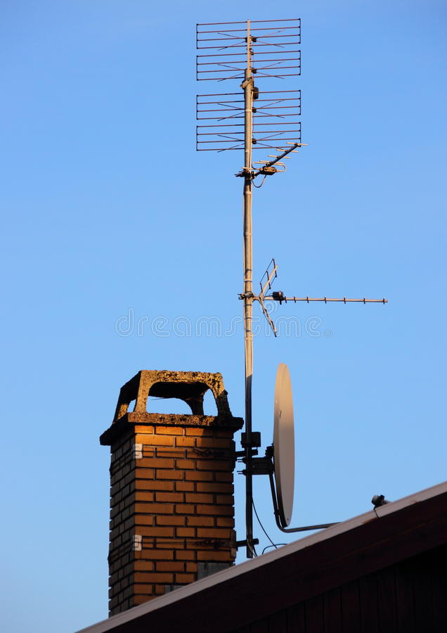 Antenna and satellite dish on a chimney. Antenna and satellite dish mounted on a chimney stock photos